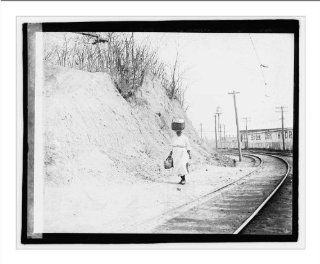 Historic Print (L) [African American woman with basket on head walking near railroad tracks]